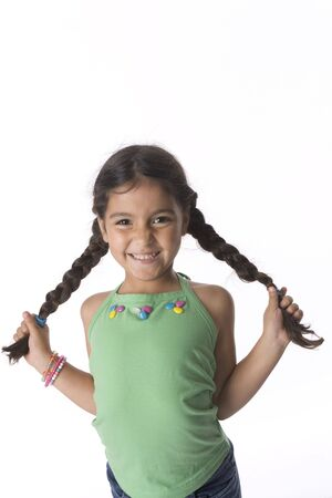 timid: Little Girl Is Showing Her Pigtails With A Timid Expression Stock Photo