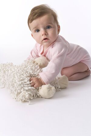 сooking: Cute Baby Girl Sitting On The Floor With Her Toy Sheep