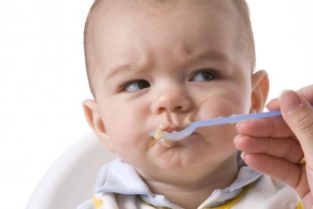 dislike: Baby Boy wordt gevoed met een lepel en heeft een afkeurende Expression