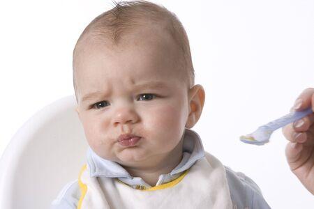 disapproving: Baby Boy � alimentato con un cucchiaio e Has A disapprovazione Expression Archivio Fotografico