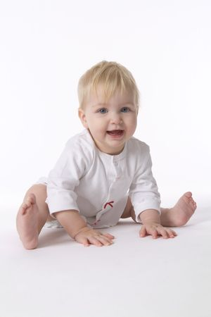 supple: Happy Pliant Baby Girl Is Sitting On The Floor On White Background