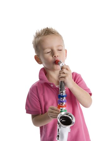Little boy is playing a toy saxophone on white background photo