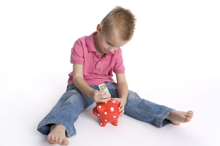 billet: Little Boy Is Sitting On The Floor And Puts A Dollar Billet In A Piggy- Bank