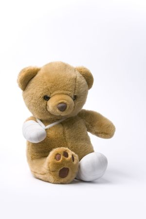 Teddy Bear With Two Broken Legs On White Background photo