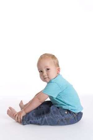 excercise: Toddler Boy Sitting On The Floor Holding His Feet Doing Fitness Excercise