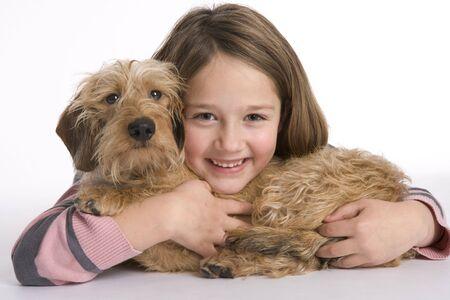 ni�as sonriendo: Retrato de una ni�a peque�a y su perro de mascota en el fondo blanco Foto de archivo