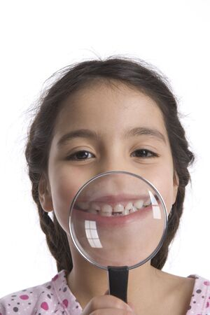 Little Girl Shows Her Teeth Through A Magnifying Glass photo