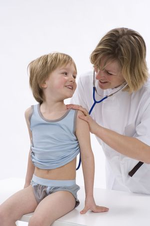 listening to heartbeat: Female doctor is listening to the heart rhythm of a little boy with a stethoscope