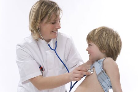 Female doctor is listening to the heart rhythm of a little boy with a stethoscope photo