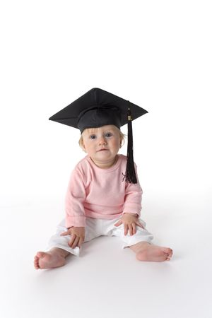 Baby girl is sitting on the floor with a graduation cap on white background