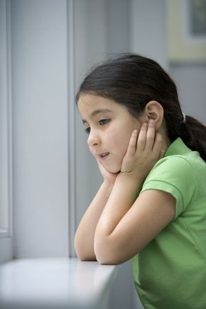 Little girl is looking out of the window with a sad face photo