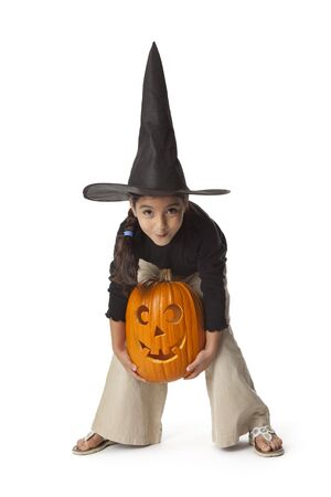 Little girl is lifting a Halloween pumpkin  photo