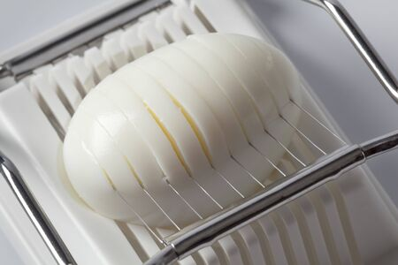 SLICER:  Hard boiled egg in an egg slicer Stock Photo