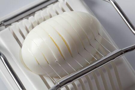 slicer:  Hard boiled egg in an egg slicer Stock Photo