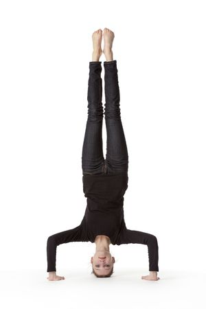Teenage girl in headstand on white background photo