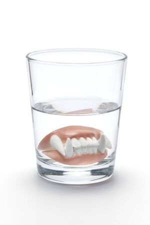 prothesis: Dental prothesis of a vampire in a glass of water on white background Stock Photo