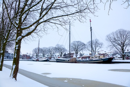 Classic boat in a frozen canal in winter in Holland photo