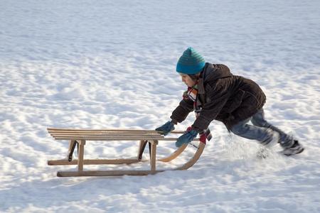 niño empujando: El niño pequeño que empuja subidas de trineo en la nieve