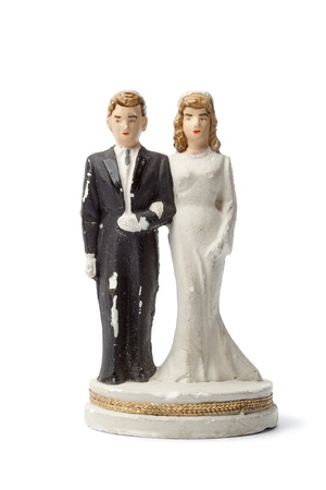 figurines:  Old damaged plaster bride and groom cake topper isolated on white background