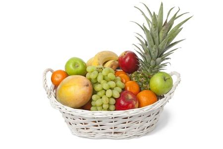 Cesta de blanca con una variedad de frutas frescas sobre fondo blanco