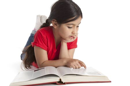 Eight year old girl reading a book on white background Stock Photo - 9637906