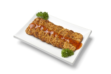 Slices fried tempeh with chili sauce on a dish on white background