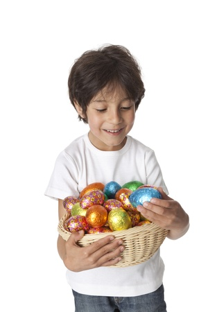Little boy with a basket of chocolate Easter eggs on white background photo
