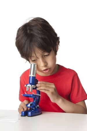 Little boy looking through a microscope on white background Stock Photo - 9637756