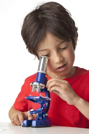 Little boy looking through a microscope on white background Stock Photo - 9638720