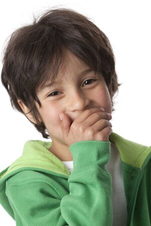 Little boy laughing behind his handon white background photo