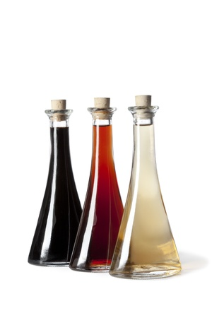 Three bottles with different type of vinegar on white background