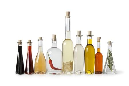 Botellas con diferentes tipos de aceite y vinagre en el fondo blanco Foto de archivo