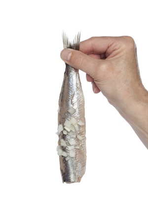 Hand holding a fresh herring with onions on white background