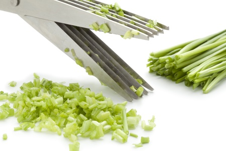 chives: Herb scissors cutting chives on white background Stock Photo