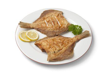 plaice: Dish with fried plaice, lemon and parsley on white background Stock Photo