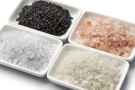Four types of salt in white dishes close up
