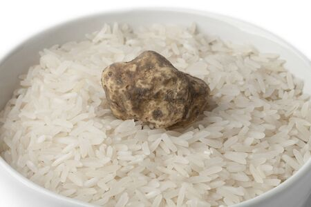 white truffle: Cup of raw rice with fresh white truffle on white background
