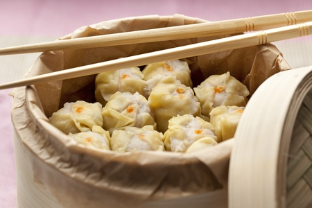 porc: Chinese Dim Sum in a steaming basket with chopsticks