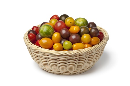 homegrown:  Basket with different color homegrown organic tomatoes on white background Stock Photo