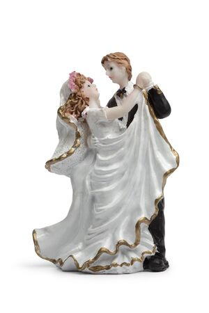 Bride and groom dancing, old cake topper on white background photo