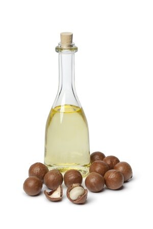 nut shell:  Bottle with Macadamia oil and nuts on white background Stock Photo