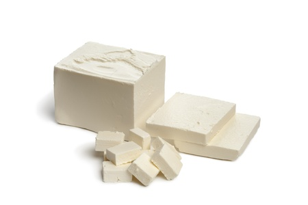 Verse feta kaas met plakjes en blokjes op witte achtergrond