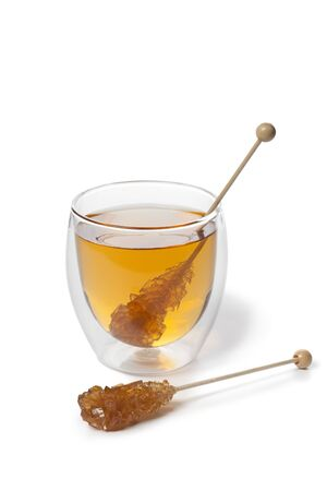 candy stick:  Tea with brown Rock candy stick on white background Stock Photo