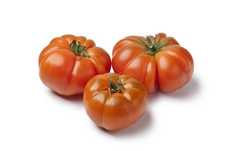 coeur: Organic Coeur de Boeuf tomatoes on white background