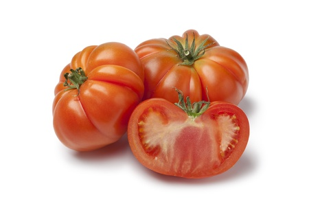 Whole and half  organic Coeur de Boeuf tomatoes on white background