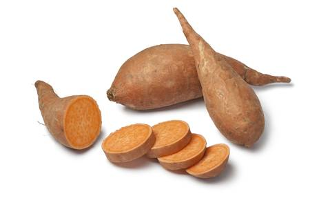 batata: Las patatas dulces y las rebanadas en el fondo blanco