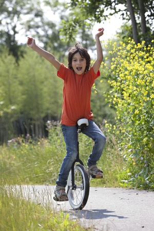 hurray: Boy balancing on a unicycle in the park Stock Photo