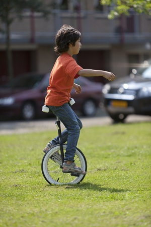 Boy balancing on a unicycle in the park Stock Photo