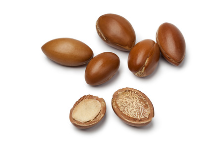 Whole and half Moroccan Argan nuts on white background Stock Photo