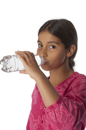 11 years: Young teenage girl drinking fresh water from a bottle on white background